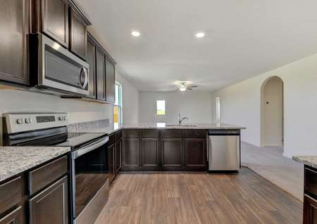 Frio kitchen with granite counters, stainless steel appliances and brown cabinetry