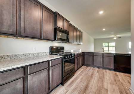 Granite counters, vinly wood-style flooring, black appliances, and dark brown cabinets in the kitchen of the Driftwood model