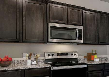 Staged kitchen with brown cabinets, gray granite and a center island with bar stools.