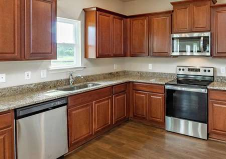 Recessed lighting, crown molding on light brown cabinets, granite countertops, vinyl wood-style flooring, and stainless steel appliances in the Hartwell model