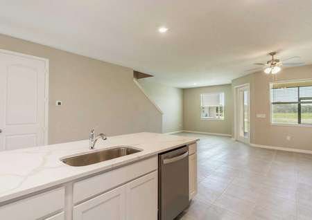 The kitchen of the Sorrento floor plan that has quartz countertops, white cabinets, a dishwasher and a view of the living room.