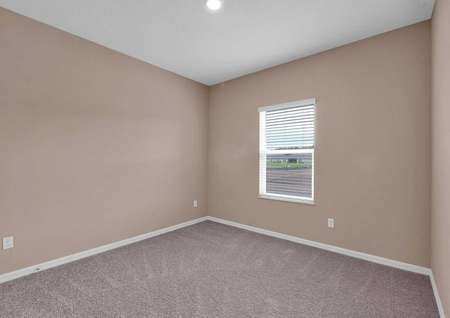 Carpeted secondary bedroom with one window and recessed lighting.