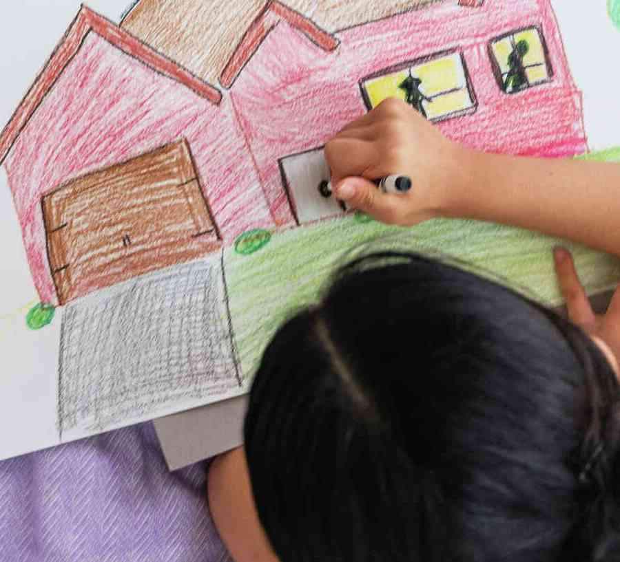 Girl coloring photo of home on rug.