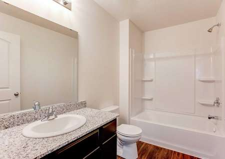 Nicollet bathroom completed with white fixtures, granite counters, and brown vanity cabinet