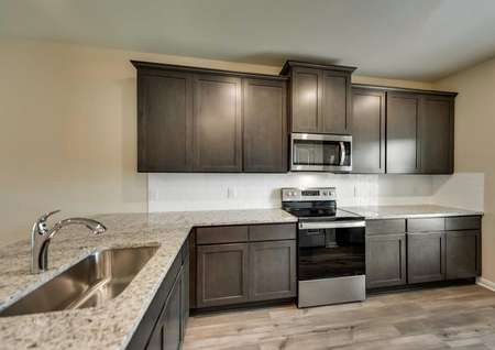 Kitchen with white tile back splash, brown cabinets and stainless steel appliances.