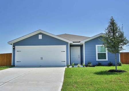 Trinity single-family home with blue siding, white trim and garage door, and green grass in yard