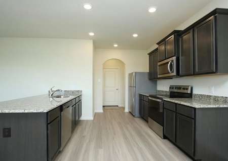 Find polished granite counters, dark espresso cabinets, recessed lighting and stylish plank flooring in the beautiful kitchen of the Mesquite by LGI Homes.