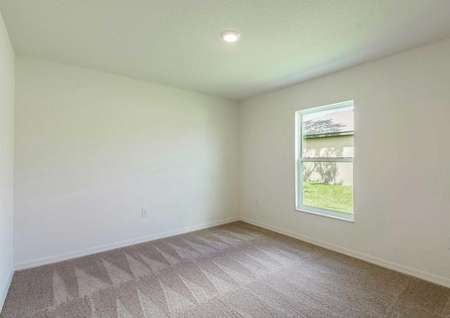 A single hung window and a ceiling light fixture in the carpeted spare bedroom of the Cocoa floor plan.
