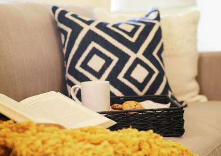 Trace model home with light color couch, black and white patterned pillow, and open book