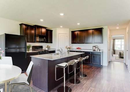 Hennepin model home staged with 3 modern bar stools, small round white table with white chairs in the dining area, and kitchen decorations on the counters
