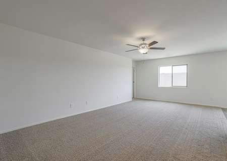 Living area of the Benson plan with ceiling fan, tan carpet and natural light from the window.